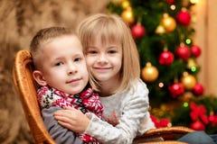 Zwei kleine Kinder im Hintergrund des Weihnachtsbaums Lizenzfreies Stockbild