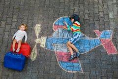 Zwei kleine Kinder, Kinderjunge und Kleinkindmädchen, die Spaß mit mit Flugzeugbildzeichnung mit bunten Kreiden an haben stockbild
