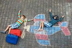 Zwei kleine Kinder, Kinderjungen, die Spaß mit mit Flugzeugbildzeichnung mit bunten Kreiden auf Asphalt haben freunde stockfoto