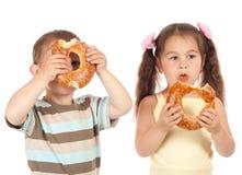 Zwei kleine Kinder mit Bageln lizenzfreies stockfoto