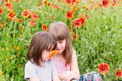 Zwei kleine Kinder mit Blumen lizenzfreie stockfotografie