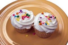 Zwei kleine Kuchen auf einer gelben Platte Stockbild