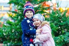 Zwei kleine lächelnde Kinder, Junge und Mädchen mit Weihnachtsbaum Stockfoto