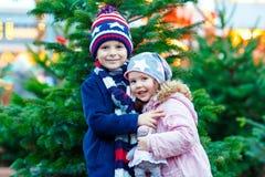 Zwei kleine lächelnde Kinder, Junge und Mädchen mit Weihnachtsbaum Lizenzfreie Stockbilder
