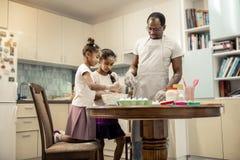 Zwei kleine lustige Mädchen, die aufgeregten kochenden kleinen Kuchen glauben stockbilder