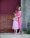 Zwei kleine Mädchen in den rosa Kleidern Stockbilder