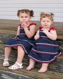 Zwei kleine Mädchen in den Sonnekleidern Lizenzfreies Stockfoto