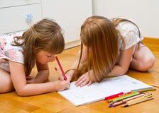 Zwei kleine Mädchen, die auf den Boden zeichnen stockbilder