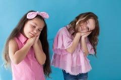 Zwei kleine Mädchen, die den Schlafschlaf nett spielen stockfoto