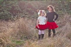 Zwei kleine Mädchen, die in der Landschaft aufwerfen Stockbild
