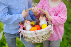 Zwei kleine Mädchen, die einen Korb von Ostereiern halten Lizenzfreie Stockfotografie