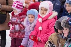 Zwei kleine Mädchen, die in einer Menge von Kindern auf der Feier der neuen Jahre der Kinder in der Straße stehen Lizenzfreie Stockfotos