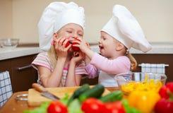Zwei kleine Mädchen, die gesunde Nahrung auf Küche zubereiten Lizenzfreie Stockbilder