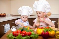 Zwei kleine Mädchen, die gesunde Nahrung auf Küche zubereiten Lizenzfreies Stockfoto