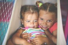 Zwei kleine Mädchen, die im Spielplatz spielen Kleine Schwestern, die t spielen Lizenzfreie Stockfotos