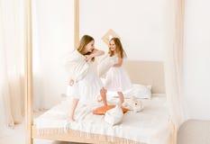 Zwei kleine Mädchen, die mit Kissen auf dem Bett kämpfen lizenzfreies stockbild