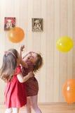Zwei kleine Mädchen, die mit luftigen Kugeln spielen Lizenzfreie Stockbilder