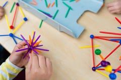 Zwei kleine Mädchen, die mit vielen buntem Plastik spielen, haftet ki Stockbilder