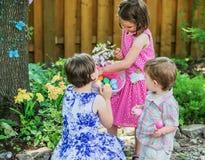 Zwei kleine Mädchen, die Ostereier in einem Korb betrachten Stockbild