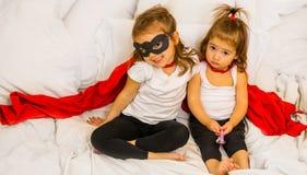 Zwei kleine Mädchen, die Superhelden spielen stockfotos