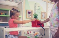 Zwei kleine Mädchen, die zusammen im Spielplatz spielen Kleines Mädchen giv Stockfotografie