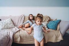 Zwei kleine Mädchen in einem Raum auf der Couch Lizenzfreie Stockfotografie