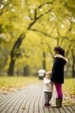 Zwei kleine Mädchen am Herbstpark lizenzfreie stockbilder
