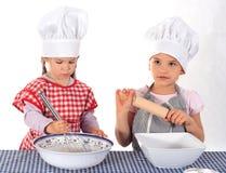 Zwei kleine Mädchen im Kochkostüm Stockfotografie