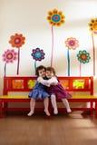Zwei kleine Mädchen Lächeln und Umarmung an der Schule lizenzfreies stockbild