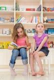 Zwei kleine Mädchen lesen ein interessantes Buch Stockfotografie