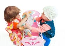 Zwei kleine Mädchen teilen eine Puppe Lizenzfreie Stockfotografie