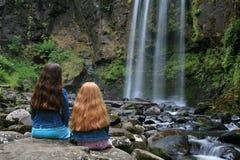 Zwei kleine Mädchen und ein Wasserfall Stockfoto