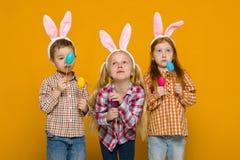 Zwei kleine Mädchen und Junge mit den Osterhasenohren, die bunte Eier halten lizenzfreies stockbild