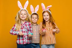 Zwei kleine Mädchen und Junge mit den Osterhasenohren, die bunte Eier halten lizenzfreies stockfoto