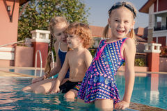 Zwei kleine Mädchen und kleiner Junge, die im Pool spielen Stockfotos
