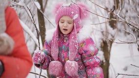 Zwei kleine Mädchen werden im schneebedeckten Wald verwickelt stock video
