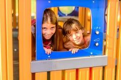 Zwei kleine Mädchen, die auf dem Spielplatz spielen Lizenzfreie Stockfotos