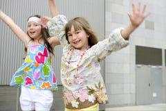 Zwei kleine Mädchen, die in die Stadt tanzen Stockbild