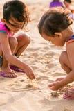 Zwei kleine Mädchen, die Strandsande spielen Stockfotos