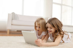 Zwei kleine Mädchen mit Tabletten-PC zu Hause Stockfotografie