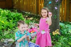 Zwei kleine Mädchen und ein Junge mit ihren Ostereiern Stockbild