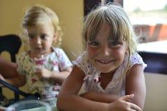 Zwei kleine Schwestern der kleinen netten Mädchen sitzen an einem Tisch Stockbilder