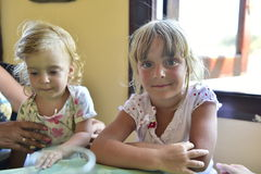 Zwei kleine Schwestern der kleinen netten Mädchen sitzen an einem Tisch Lizenzfreie Stockfotografie