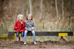 Zwei kleine Schwestern, die auf einer Bank sitzen Lizenzfreie Stockbilder