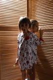 Zwei kleine Schwestern, die in den Pyjamas gekleidet werden, verstecken sich im Wandschrank mit Holztüren lizenzfreies stockfoto