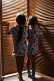 Zwei kleine Schwestern, die in den Pyjamas gekleidet werden, verstecken sich im Wandschrank mit Holztüren lizenzfreie stockbilder