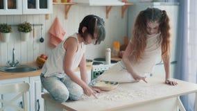 Zwei kleine Schwestern, die in der Küche, zeichnend mit Mehl auf Tabelle, Zeitlupe kochen stock footage