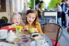 Zwei kleine Schwestern, die Eiscreme in einem Café im Freien essen Stockfoto