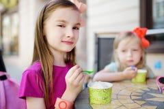 Zwei kleine Schwestern, die Eiscreme in einem Café im Freien am Sommertag essen Stockfotografie