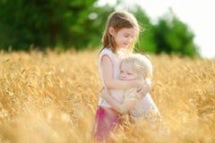 Zwei kleine Schwestern, die glücklich auf dem Weizengebiet gehen stockfotografie